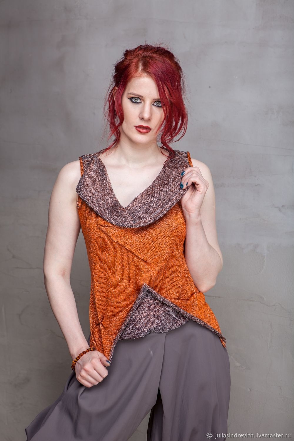 S_012 Knit top with kangaroo pocket and fold-over collar front with a flared back lace up, pleats on the chest, color orange/silver. S_043 Sewn pants Crazy Legs, gray color.
