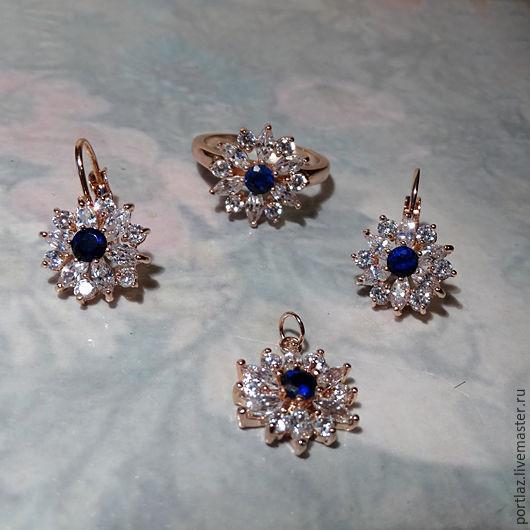 Нежный изящный комплект украшений ручной работы в виде цветов - серьги, подвеска и кольцо с  темно-синим сапфиром и бриллиантовыми фианитами в оправе цвета розового золота.
