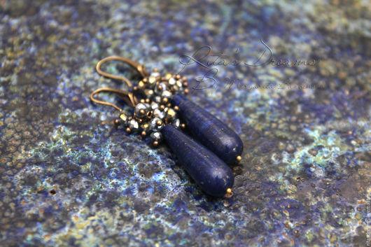 Серьги-капли из прекрасного лазурита насыщенного темно-синего цвета с золотисто-бронзовыми вкраплениями и маленьких граненых мерцающих стеклянных бусинок.