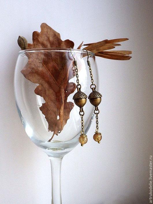Небольшие изящные серьги выполнены из фурнитуры цвета античной бронзы в виде желудей и бусин агата бежевого цвета. Длина серег 6 см.