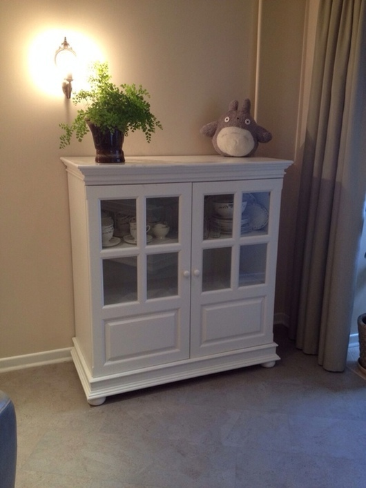 Белый буфет для хранения посуды, полотенец и других вещей. Имеет три вместительные полки. Фасады дверец со стеклянными вставками. Буфет не слишком высокий, что позволяет использовать столешницу функционально.