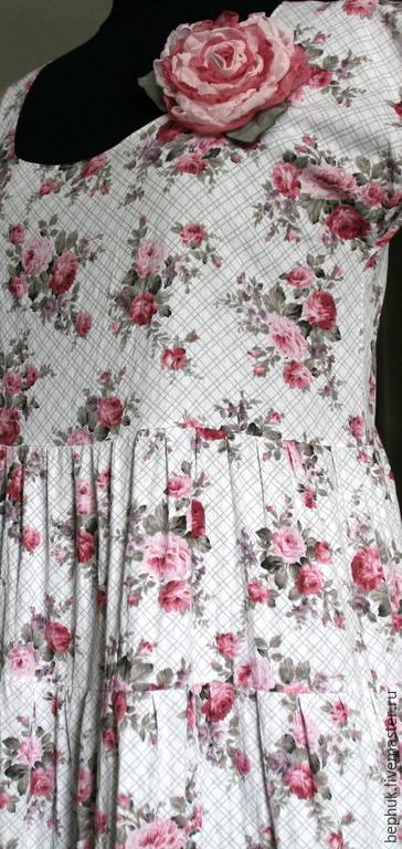 Платье  сшито в романтичном стиле, его навевает сам рисунок мелких розочек на фоне двойной клетки, нарисованной контурными тонкими двойными линиями бледно сиреневого цвета.