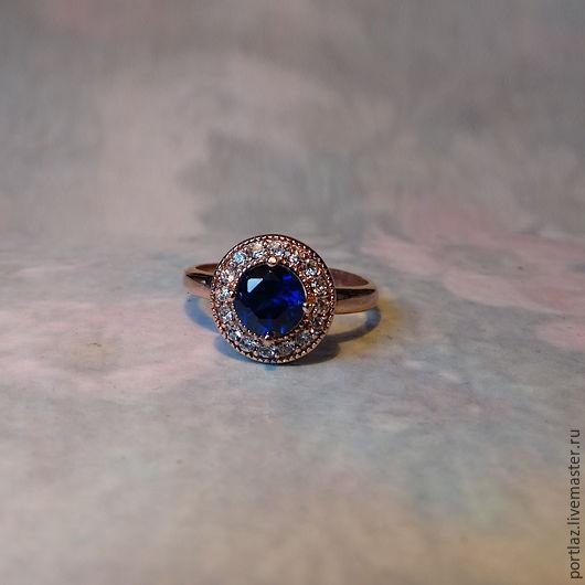Позолоченное розовым золотом 585 пробы кольцо с сапфиром и фианитами выглядит, как золотое. 17 размер.