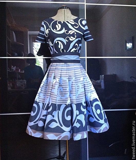Спереди юбка украшена приютом в соответствии с верхней частью платья