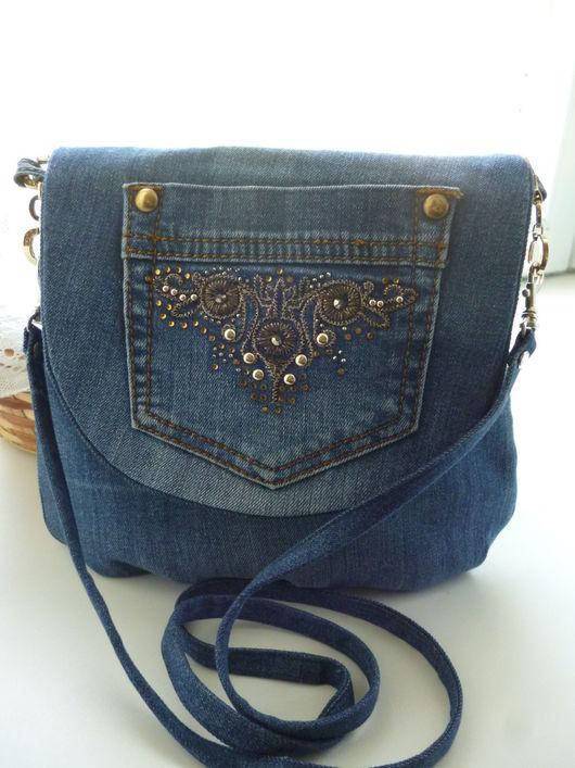 Джинсовая сумочка через плечо.Небольшая компактная форма создает легкость и удобство. Внутри одно отделение с 2 кармашками на молнии и резинке.Длинный ремешок через плечо.Застежка - магнитная кнопка.