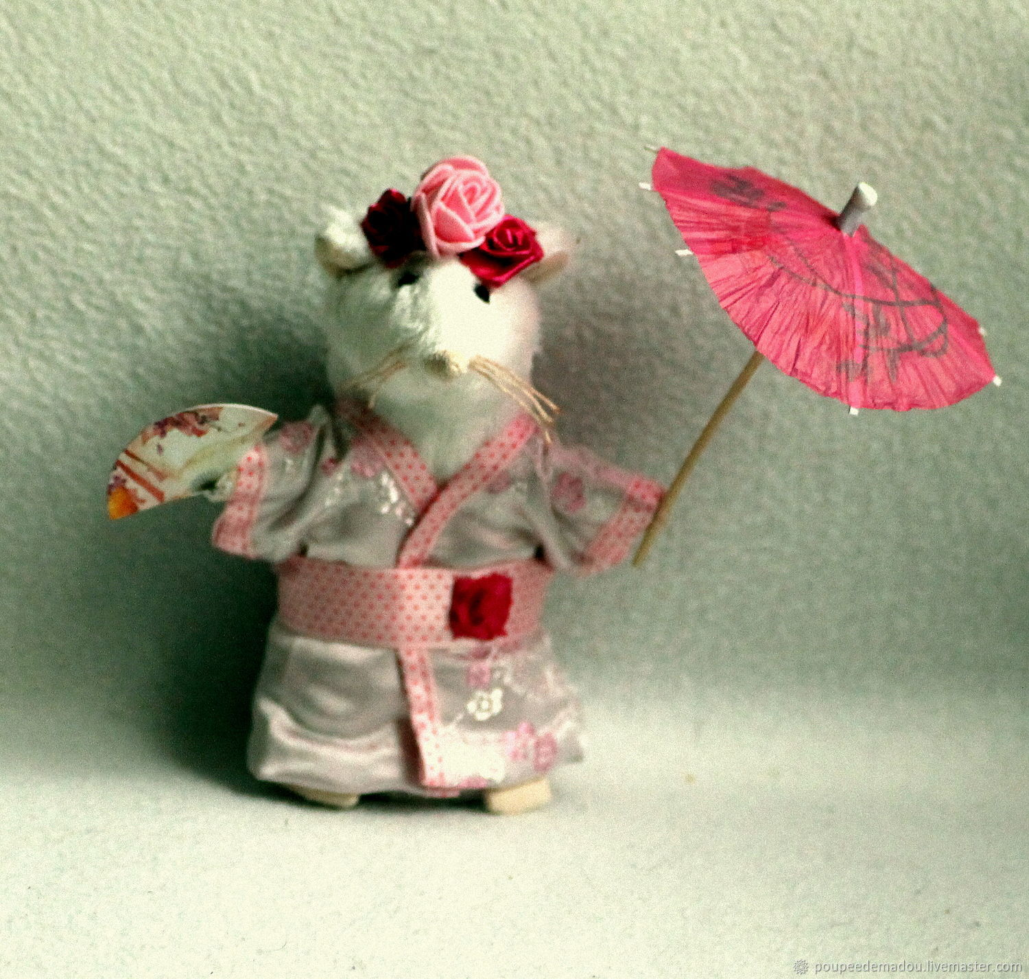 Lia is a white stuffed mouse. She is a Japanese woman, wearing a pink kimono, held in place by a wide belt of polka-dot ribbon adorned with a rose. On his head his hairstyle is made with three roses.