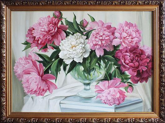 букет из свежих розовых и белых пионов на белом столе в прозрачной рюмке-вазе . Беая драпировка свисает со стола.