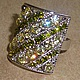 со вспышкой Эффектное крупное кольцо белого металла  от Inesse M со стразами Сваровски лимонно-желтого и желто-зеленого цветов.