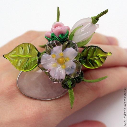 Кольцо перстень выполнено на основе с природным, натуральным розовым кварцем. Для цветочной композиции использовались стеклянные бусины-цветы, ручной работы в технике лэмпворк lampwork (лэмпворк)  Гармонично дополняют композиции бусины из граненого стекла, и листочки лэмпворк, также выполненные вручную