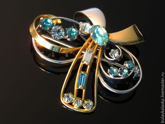 Lustern 12K Gold Винтажная брошь в виде стилизованного банта, украшенная кристаллами изумрудного и прозрачного цвета. Украшение маркировано 1/20 12 К , (1/20 изделия составляет 12-каратное `накатанное